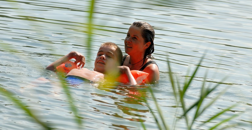 Junge mit Schwimmflügeln schwimmt mit Betreuerin