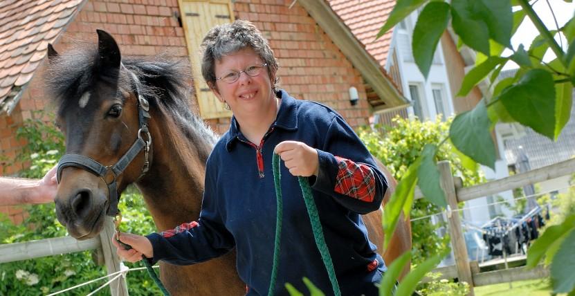 Frau führt ein Pferd