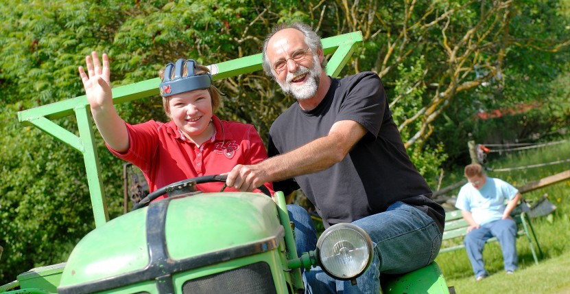 Herr Rist fährt mit einem Mädchen Traktor